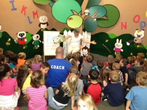 Image of an adult male sitting among children at a storytime