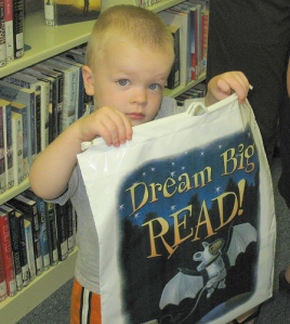 "Photo of a young boy with a sign that says ""Dream Big, Read!"""