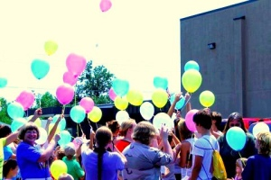 Photo of Marie Vallee releasing balloons with young patrons at a library program