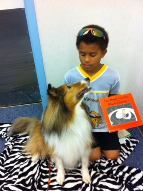 Image of a young boy reading to a dog