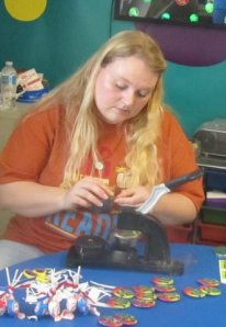 "Drexel library assistant, Amber Bodenhamer, crafts ""I'm a Bookworm"" pin as prizes for Summer Reading Program readers."