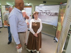 """Library of Congress Trustee, Donald Hall, discusses the new """"Stern Visitation of War in Cass County"""" exhibit with Carol Bohl, former Cass County Historical Society director."""