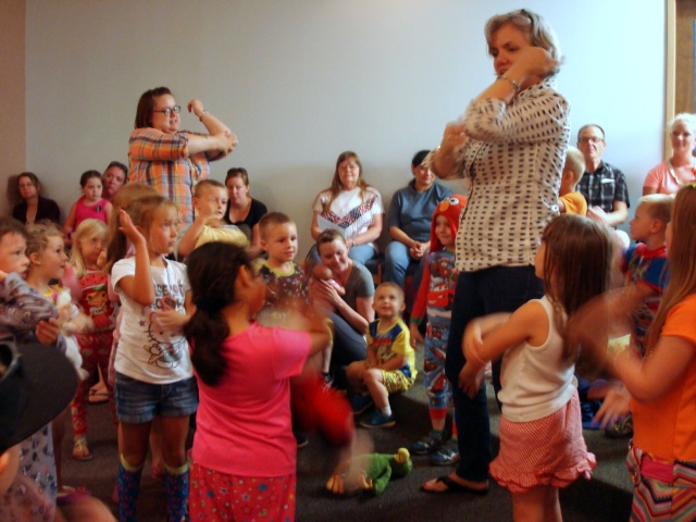 Harrisonville librarians lead young patrons in an activity at an evening pajama storytime.
